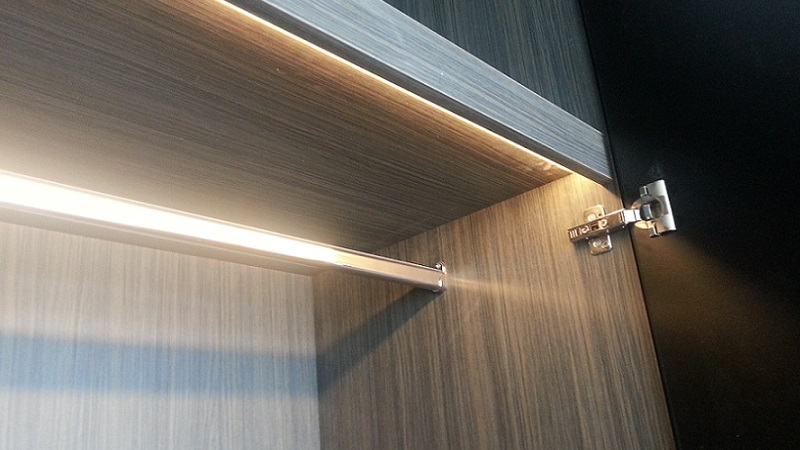 Concealed LED strip on pelmet in wardrobe cabinet activated by magnetic reed sensor door switch