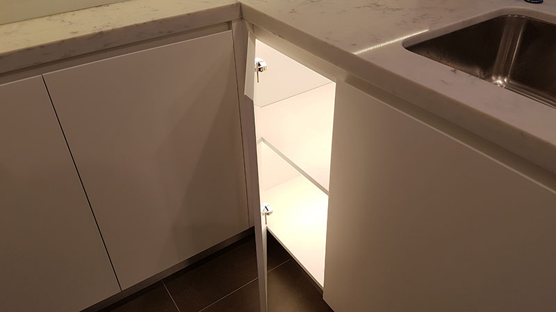 Corner kitchen cabinet with door activated LED lighting