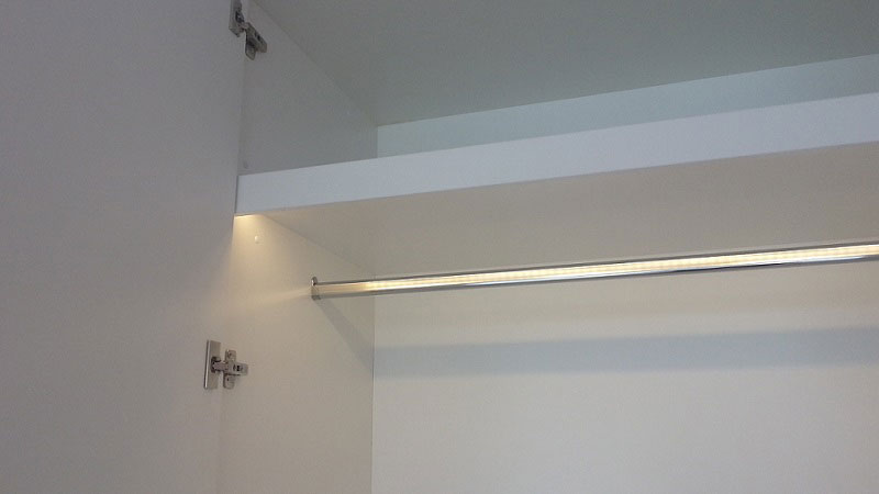 Concealed LED strip on pelmet in wardrobe cabinet activated by Lightdream's magnetic reed sensor door switch