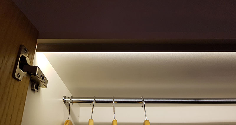 Concealed LED strip on aluminium pelmet in wardrobe cabinet activated by magnetic reed sensor door switch